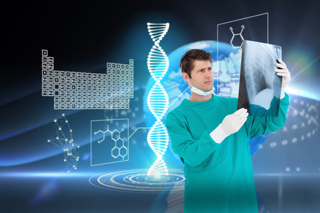 Close up of male doctor wearing coat looking at x-ray against digital earth background photo