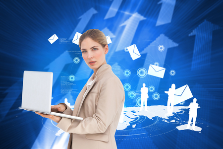 Businesswoman with a laptop against futuristic shiny arrow pointing upwards photo