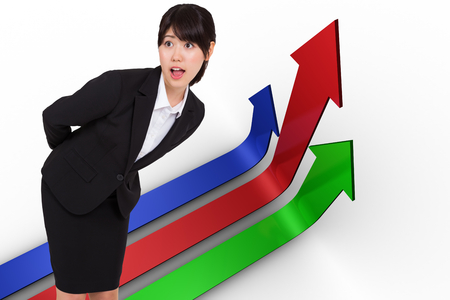 Surprised businesswoman bending against colourful arrows pointing up photo