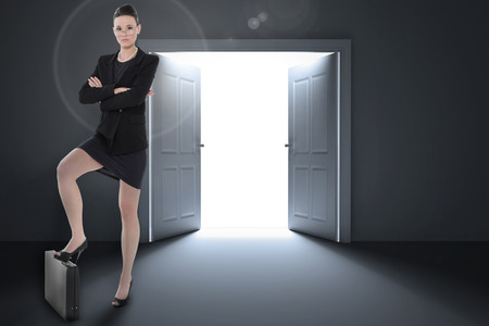 Full length of an elegant businesswoman in suit against doors opening revealing light photo