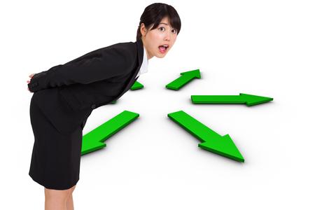 Surprised businesswoman bending against green arrows  photo