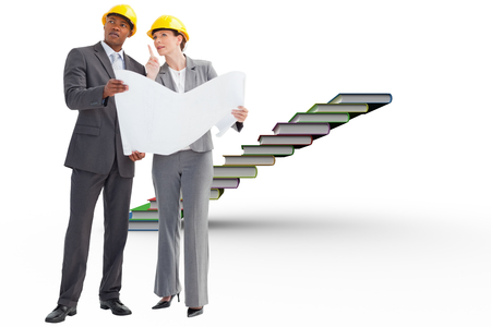 Business people wearing hard hats are discussing  against steps made from books photo