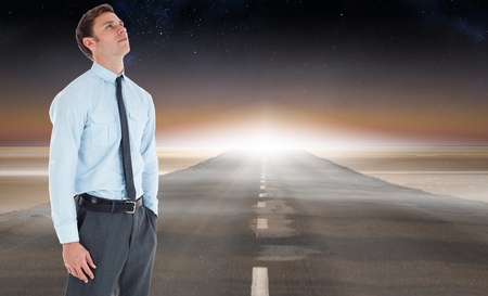 Serious businessman standing with hand in pocket against road leading out to the horizon