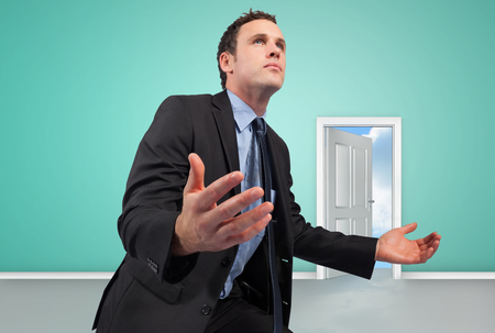Businessman posing with arms out against door opening showing blue sky photo