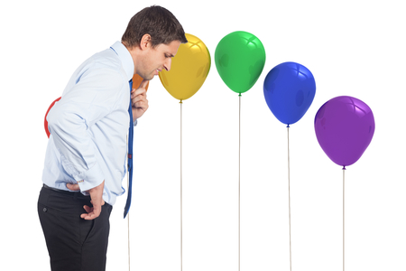Thinking businessman touching his chin against colourful balloons photo
