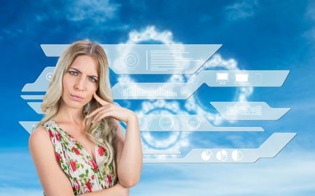 Frowning pretty blonde wearing flowered dress posing against white cogs in the sky photo