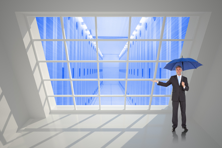 Peaceful businessman holding blue umbrella against server hallway seen through window photo