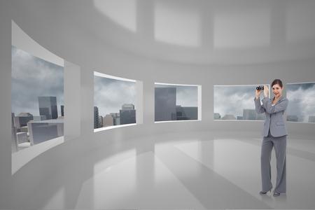 Businesswoman posing with binoculars against cityscape seen through windows photo