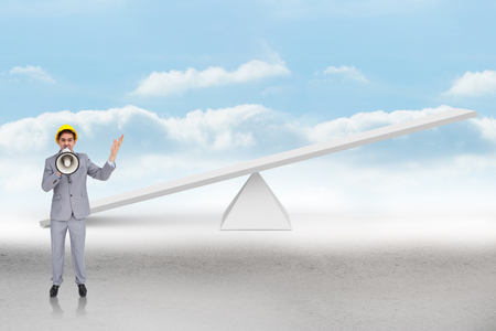 Architect with hard hat shouting with a megaphone against white scales in front of clouds photo