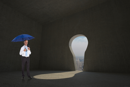 Happy businessman holding umbrella against keyhole door in dark room photo