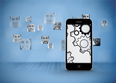 Cogs and wheels on smartphone screen against pictures of faces in blue room photo