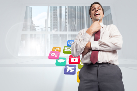 light brown hair: Thoughtful businessman holding pen to chin against computing application icons