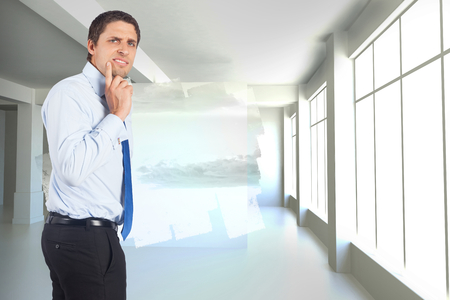 business skeptical: Thinking businessman touching his chin against abstract screen in room showing cloudy sky
