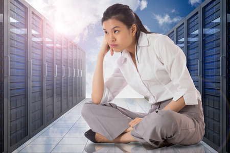 Businesswoman sitting cross legged against server hallway in the sky Stock Photo