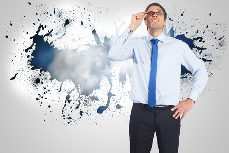 business skeptical: Thinking businessman tilting glasses against splash on wall revealing clouds