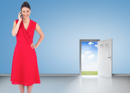 Cheerful elegant brunette in red dress on the phone posing against door opening showing blue sky photo
