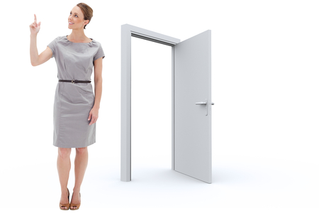open  women: Smiling woman in a dress pointing upwards against door opening
