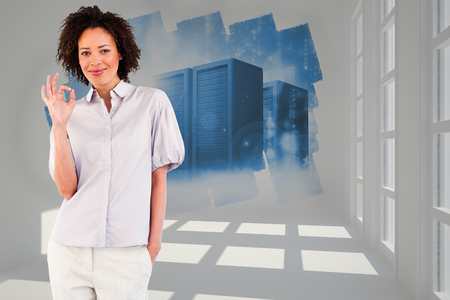 Young businesswoman showing okay sign  against abstract screen in room showing server towers photo