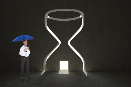 Happy businessman holding umbrella against hourglass door in dark room photo