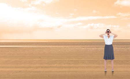 mujer mirando el horizonte: Impresionado elegante empresaria mirando a trav�s de binoculares contra el paisaje sereno