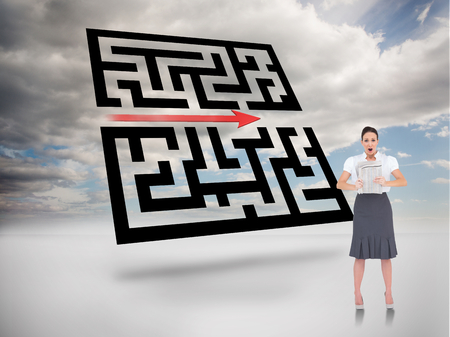 Shocked stylish businesswoman holding newspaper against maze in blue sky photo