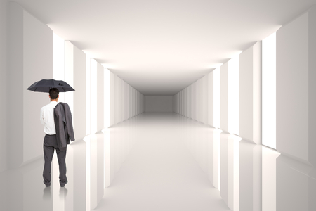 Businessman standing back to camera holding umbrella and jacket on shoulder against digitally generated room photo