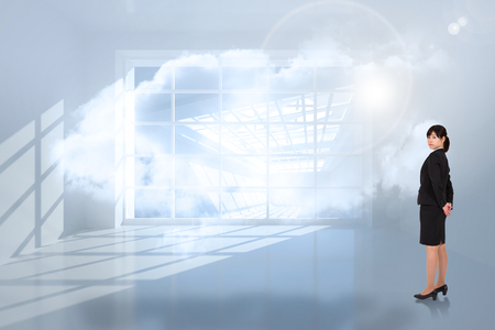 holographic: Serious businesswoman against room with holographic cloud Stock Photo