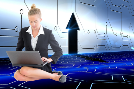 Composite image of blonde businesswoman using laptop photo