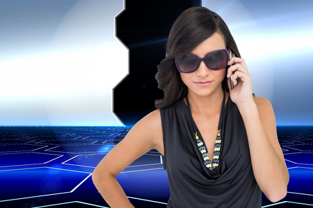 Composite image of serious elegant brunette wearing sunglasses on the phone on white background photo