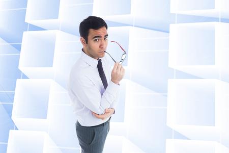 unsmiling: Composite image of unsmiling businessman holding glasses Stock Photo