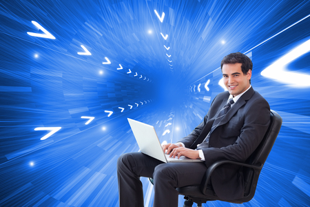 Composite image of portrait of a young businessman sitting on an armchair working with a laptop photo