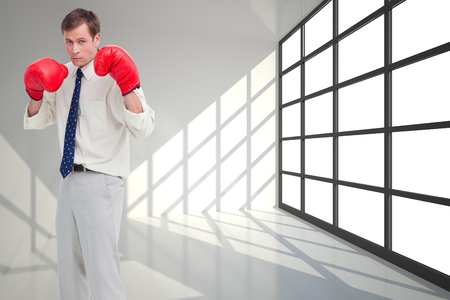 Composite image of businessman with his boxing gloves ready to fight against a white background photo