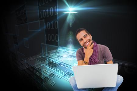 Composite image of thinking man sitting on floor using laptop and smiling on white background photo