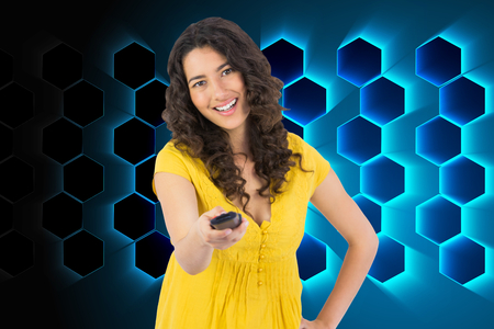 changing channel: Composite image of smiling curly haired pretty woman changing channel with remote