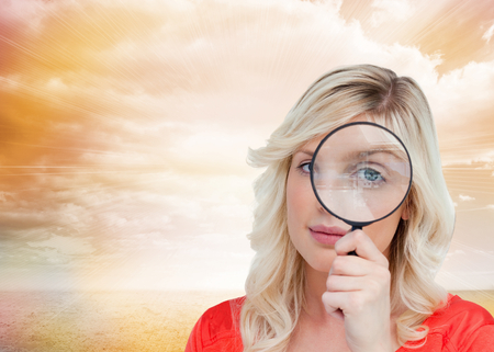 Composite image of fair-haired woman looking through a magnifying glass against a white background photo