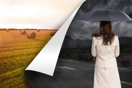 Composite image of rear view of classy businesswoman holding umbrella on white background photo