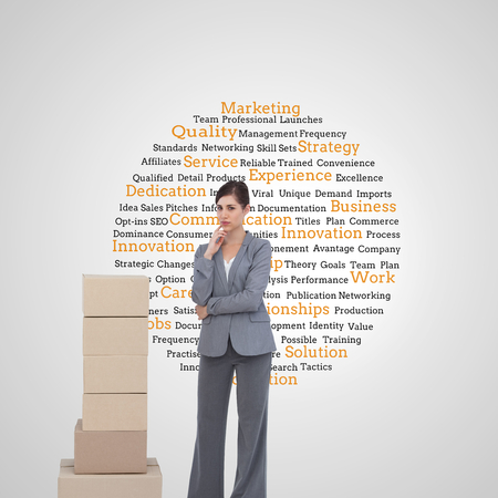 Composite image of thoughtful businesswoman posing with cardboard boxes photo