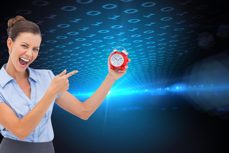 Composite image of businesswoman indicating alarm clock with finger photo