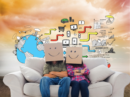 Composite image of silly employees with arms folded wearing boxes on their heads with smiley faces on a couch photo