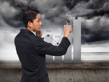 Composite image of thoughtful asian businessman pointing photo