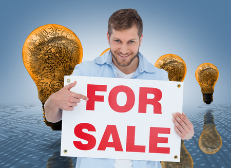 Composite image of smiling model holding a for sale sign on white background photo