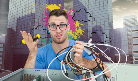Composite image of portrait of confused young it professional with screw driver and cables in front of open cpu over white background photo