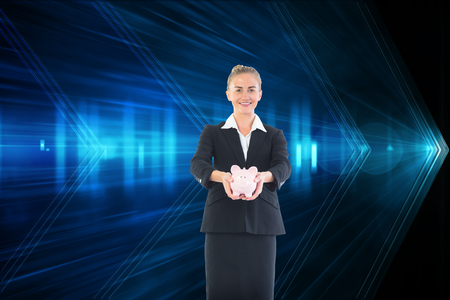 Composite image of happy blonde businesswoman holding a pink piggy bank photo