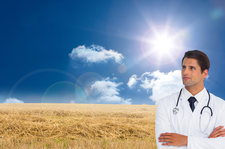 Composite image of confident doctor with arms crossed looking up on white background photo