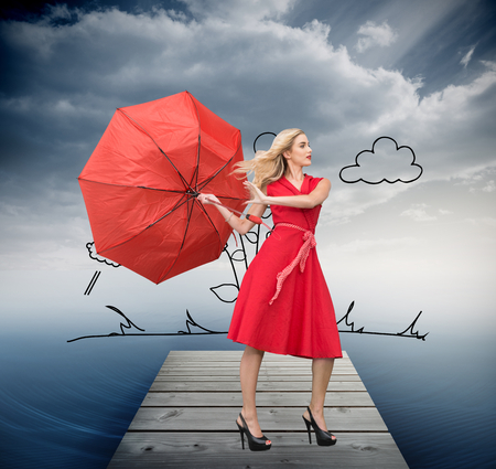 Composite image of beautiful woman posing with a broken umbrella with her leg raised photo