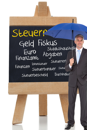 Composite image of businessman smiling at camera and holding blue umbrella against white background photo