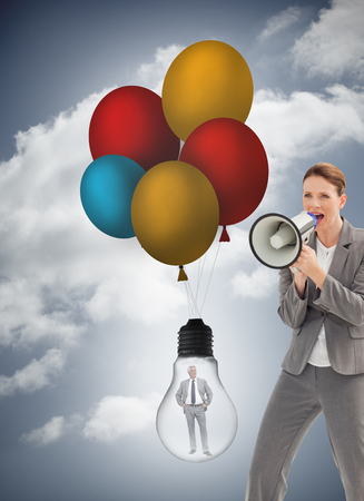 Composite image of businesswoman is talking  on a megaphone against a white background photo