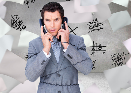 Composite image of angry businessman tangle up in phone wires isolated on a white background photo