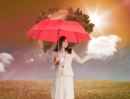 Composite image of attractive businesswoman holding red umbrella against white background photo