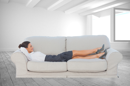 Composite image of smiling business woman lying down on the couch in the office photo
